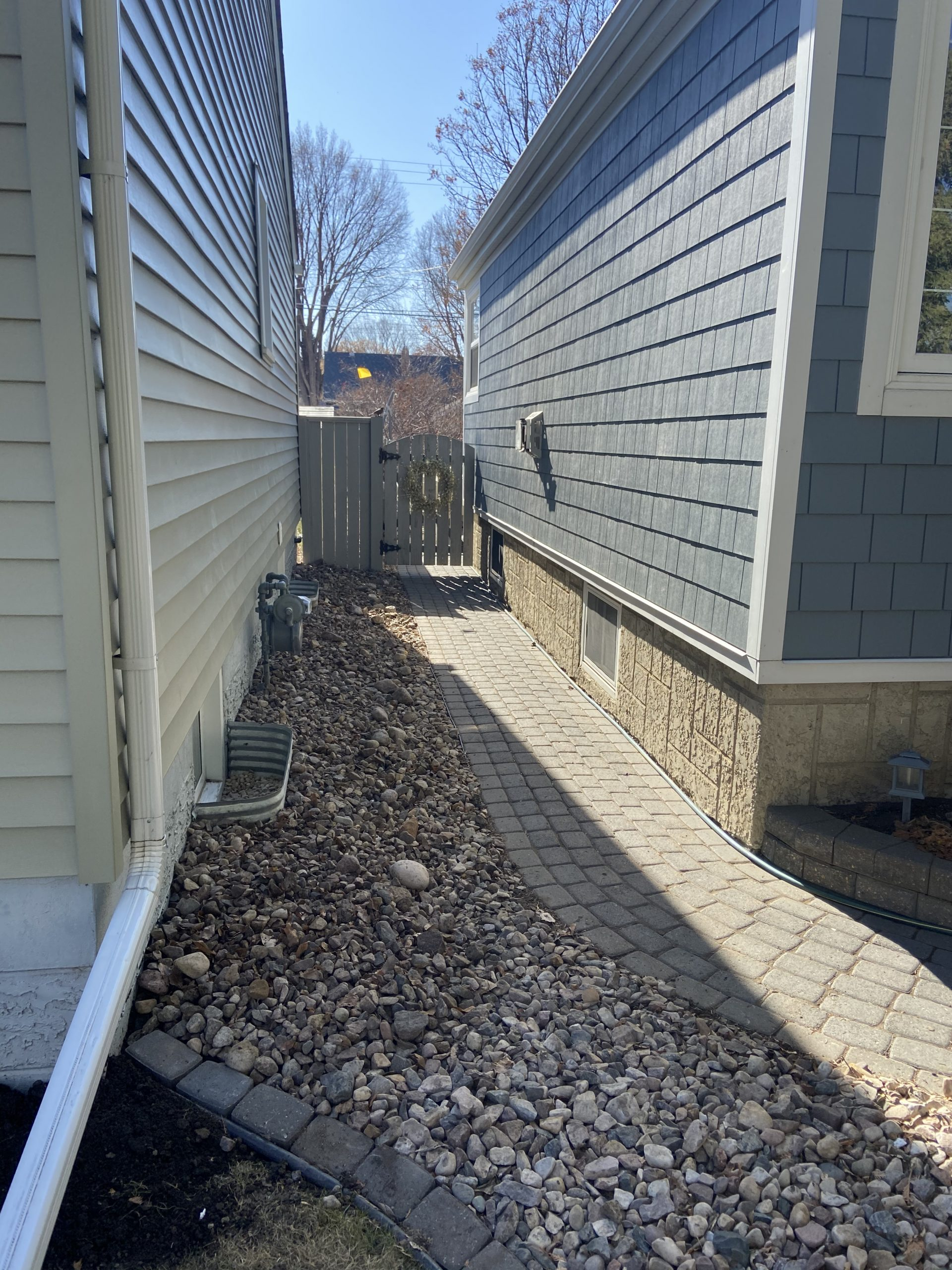 The side of a house with a rock garden, stone path and basement windows after using the hand-excavation method to waterproof it's foundation. No damages to the delicate pathway, rock garden or basement windows.