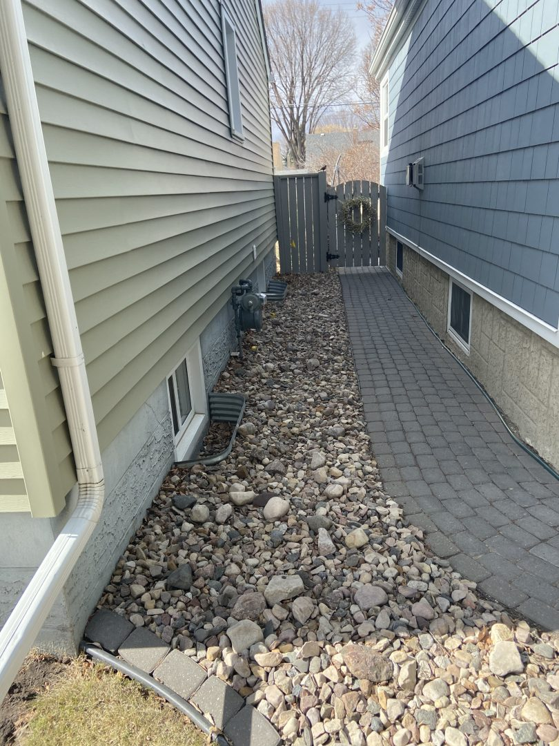 The side of a house with a rock garden, stone path and basement windows before using the hand-excavation method to repair its foundation.